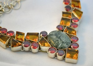 A dramatic sterling silver necklace featuring garnet, citrine and seraphinite.  Photo by the author, sockii.